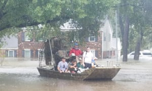 Houston residents use a boat to evacuate their homes.