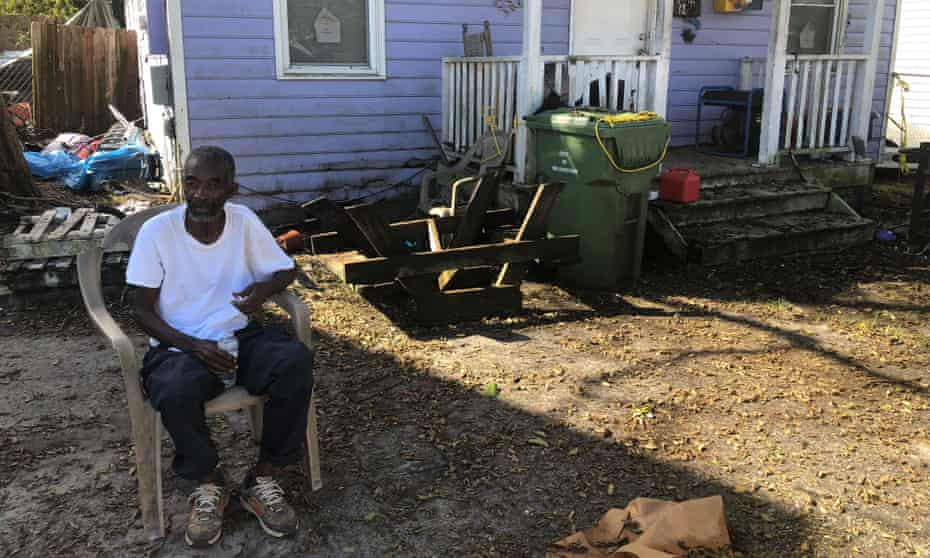 Joseph Cobbs sits in his friend's yard, manning the generator for the block in Wilmington's Northside. 'All the white people around us got power. We got none.'