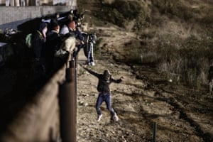 San Diego California: A migrant jumps the border fence to get into the US from Mexico