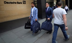 The tailors Alex Riley, left, and Ian Fielding-Calcutt carry suitbags outside the Deutsche Bank building in the City of London.
