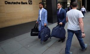 The tailors Alex Riley, left, and Ian Fielding-Calcutt carry suit bags outside the Deutsche Bank building in the City of London.