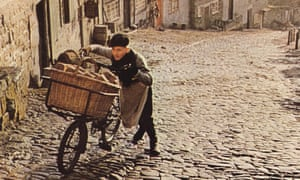 a boy pushing a bike up a cobbled road