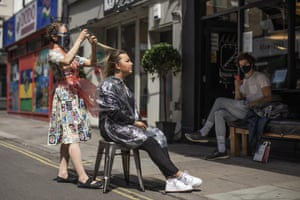 A customer has her hair cut outside at Blade Hairdressers in Soho on July 23, 2020 in London, England.