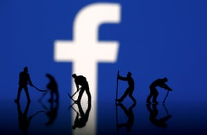 Figurines in front of the Facebook logo