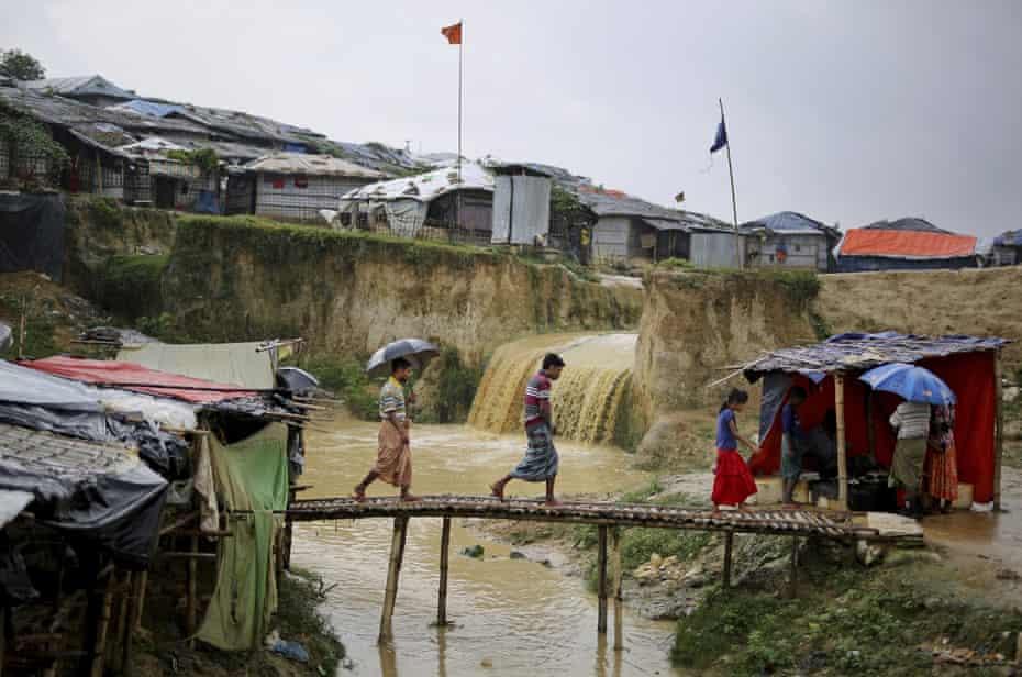Rohingya refugees cross a makeshift bamboo bridge over the sewer in Kutupalong refugee camp, Bangladesh.