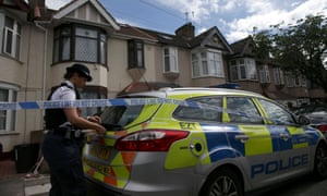 Police officer works within a cordon during a police operation at a residence in Ilford, in east London.