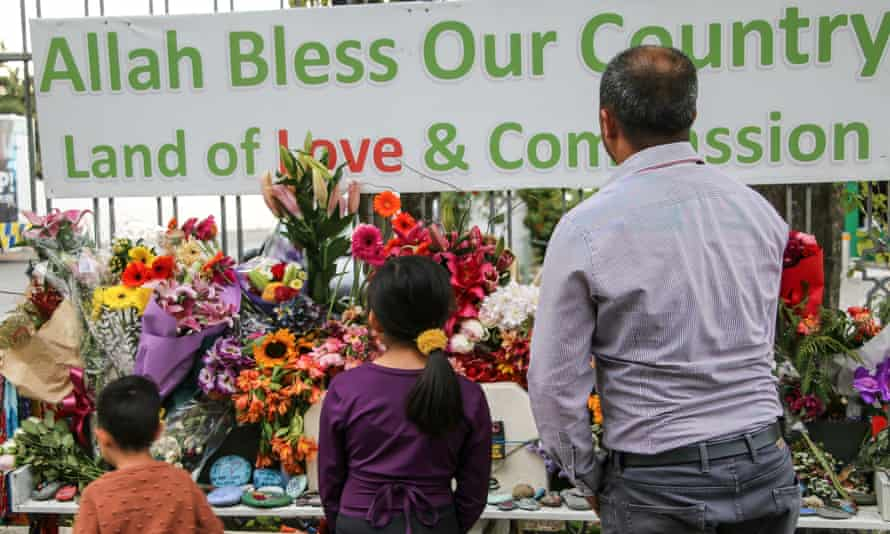A man and his children place flowers as a tribute outside the Al-Noor Mosque in christchurch