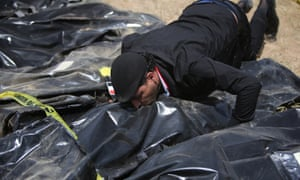 A man kisses a body bag containing the remains of people killed at the Speicher base