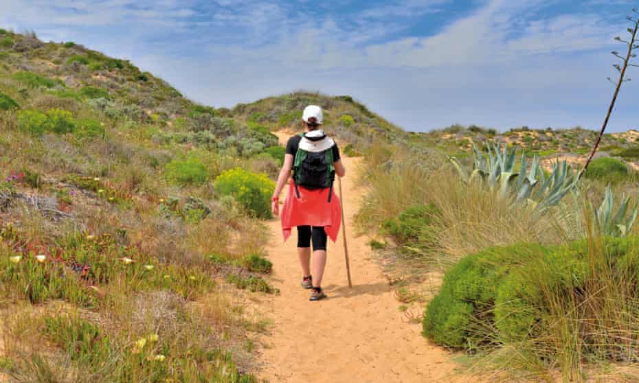 Woman with backpack crossing sand dunes of trekking trail Rota Vicentina