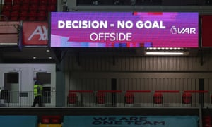 The big screen displays a VAR review message after disallowing a goal scored by Liverpool's Mohamed Salah.