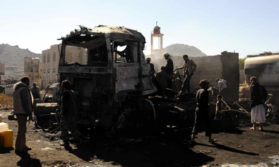Yemenis inspect the site of alleged Saudi-led airstrikes that hit vehicles carrying food items, killing at least 11 people, in the central province of Ibb, Yemen Tuesday.