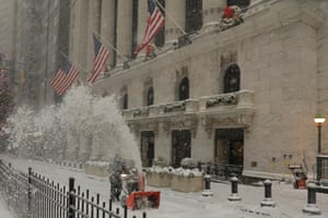 A worker clears snow from the front of the New York Stock Exchange today.