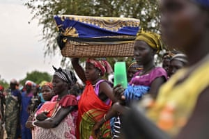 A woman balances a reed basket bearing her child on her head as she stands with fellow villagers in systemic queues as they wait to receive food rations at a village in Ayod county, South Sudan
