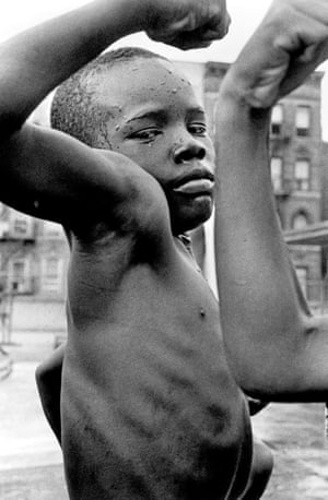 """New York City. NY. 1963. A young boy plays """"tough"""" in the streets of Harlem."""