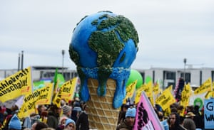 A melting planet in an ice cream cone is held up during the march in Berlin, Germany
