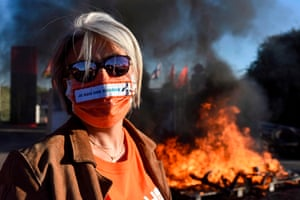 An employees of Hop!, Air France's regional low-cost airline, wears a mask displaying the slogan 'I am a source of wealth' during a protest in Bouguenais, France