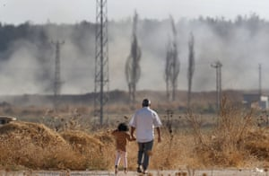 Adult and young child walking. In the background, Turkish artillery fires towards Syria