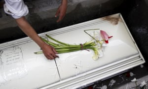 A man puts flowers on the coffin of slain environmental rights activist Berta Caceres at a cemetery in the town of La Esperanza.