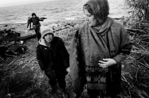 A well-dressed Syrian woman pictured arriving on the beach. The second child carries their only belongings: three umbrellas.