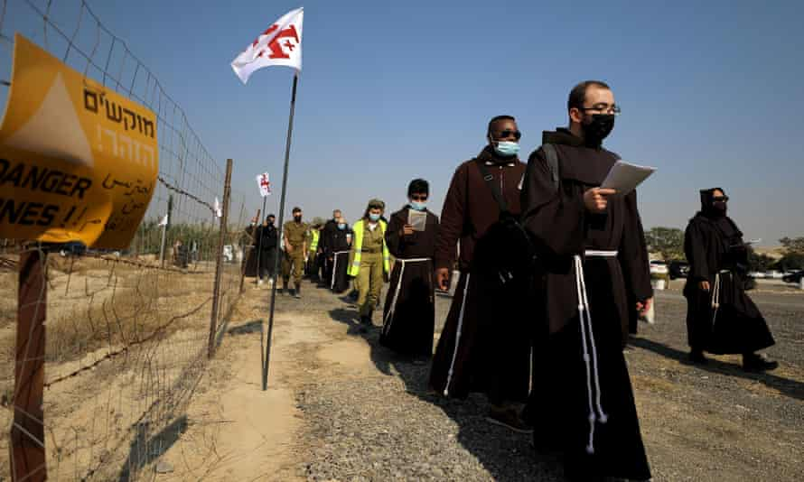 Pilgrims march towards the Jordan River to participate in a baptism ceremony at the Qasr el-Yahud site, near Jericho