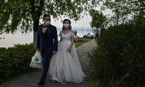 CHINA-HEALTH-VIRUSA couple wearing face masks walk after a photo-shoot next to East Lake in Wuhan, in China's central Hubei province on Sunday.