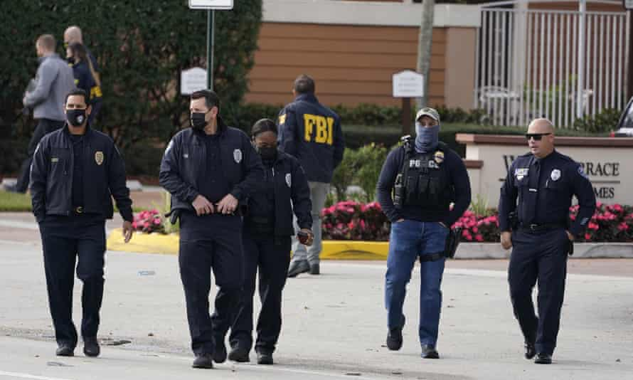 Law enforcement officers walk near the entrance to an apartment complex where a shooting wounded several FBI agents while serving an arrest warrant, in Sunrise, Florida.
