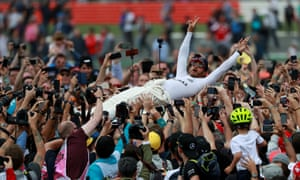 Mercedes' Lewis Hamilton celebrates his win with fans after the race by a bit of crowdsurfing.