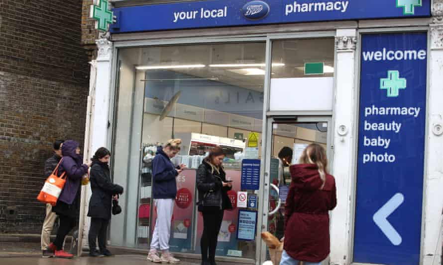 People queue outside a Boots store in London