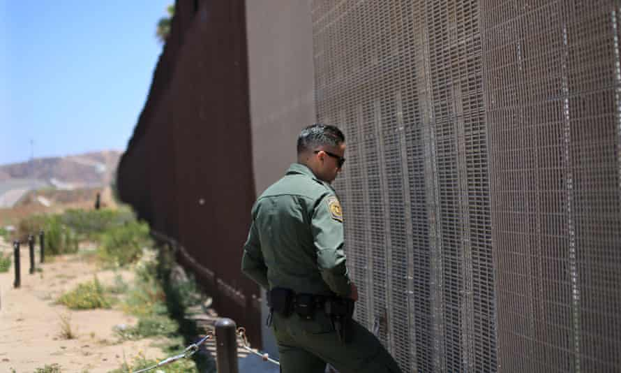 An agent patrols the US-Mexico border wall in California.