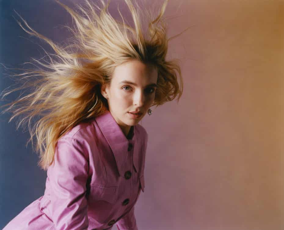 Jodie Comer in pink coat against purple and yellow background, Sept 2021