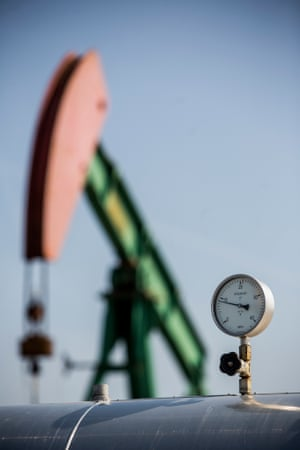 A pressure gauge sits on pipework near an oil pumping unit.