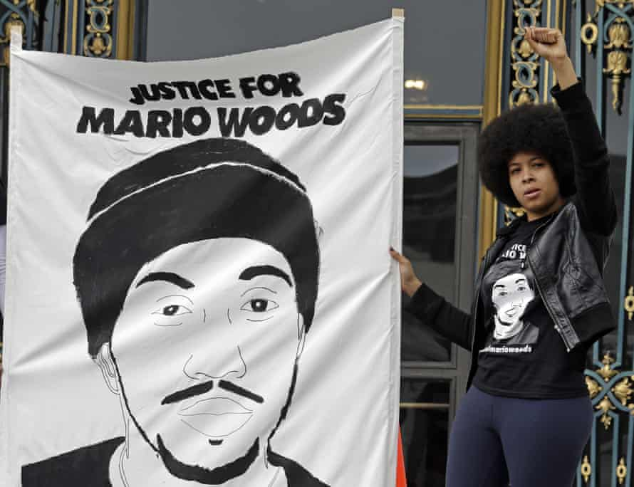 A protester stands on the steps of City Hall in San Francisco. Mario Woods was killed in a barrage of police gunfire that was caught on video.