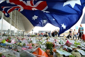 An Australian flag blows in the breeze over the thousands of floral tributes at the entrance to Schiphol Airport in the Netherlands in July 2014.