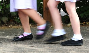 two girls walking to school, only legs and feet visible