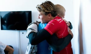 Australian surfer Mick Fanning, in blue, hugs compatriot and finals rival Julian Wilson after the attack.