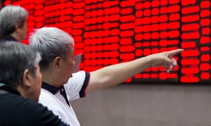 A Chinese investor points at a board of share prices