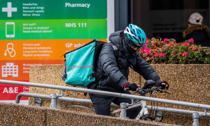 A Deliveroo rider passes an A&E department in south London.
