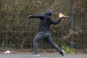 A nationalist youth throws a petrol bomb at police officers