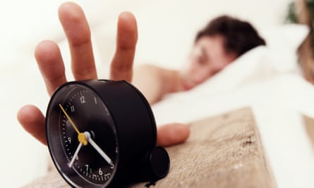 Man in bed reaching for alarm clock
