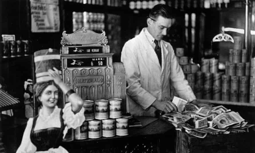 A shopkeeper counts money in a tea chest during Germany's hyperinflation era in 1922.
