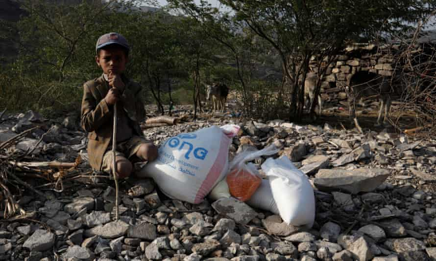A Yemeni child waits with his family's donated food ration in the remote district of Haymah