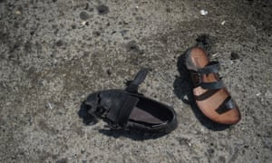 A sandal and a shoe belonging to bombing victims are seen on a road at the site of a suicide bombing attack in Kabul in March 2018