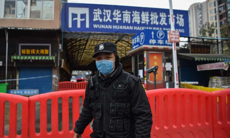 A police officer stands guard outside the shuttered Huanan seafood market in Wuhan.
