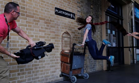 Taking off for Scots at Hogwarts … a woman poses for a photograph with the Harry Potter trolley at Kings Cross Station, in London.
