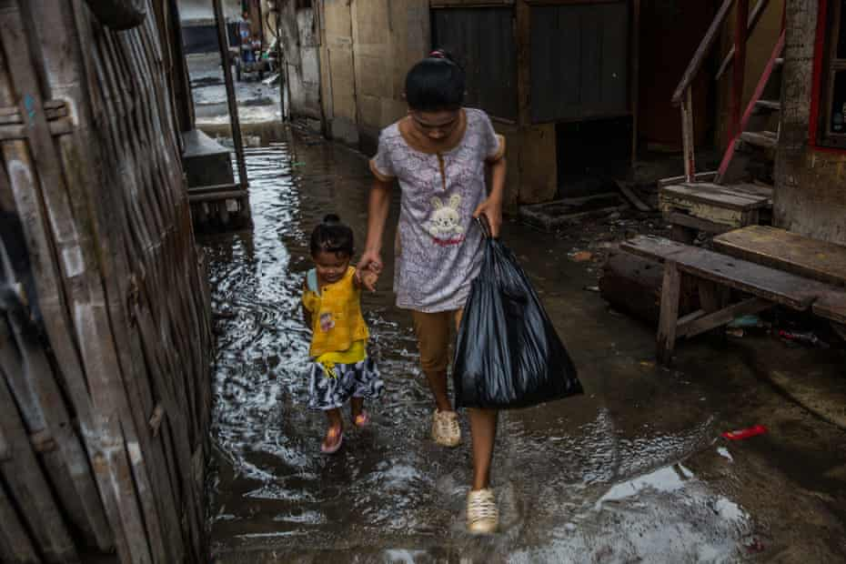 A mother and a child walk on a flooded street during a high tide in Muara Angke, North Jakarta.
