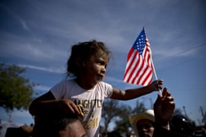 A migrant girl with a US flag sits on the shoulders of a man marching with other migrants to the Chaparral border crossing in Tijuana, Mexico on Sunday.