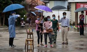 Orang-orang menunggu tes asam nukleat pada 18 Juli 2021 di Ruili, Provinsi Yunnan, Tiongkok.