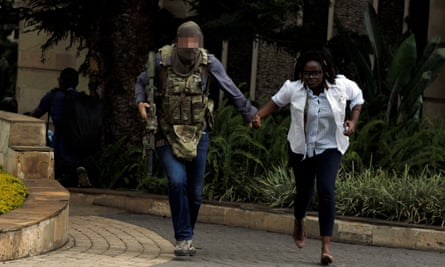 The SAS soldier helps a woman to safety.