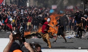 Protesters throw projectiles at police during unrest in Santiago, Chile