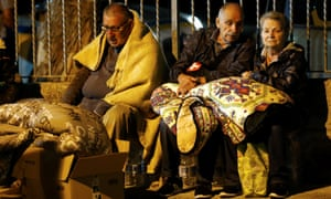 People keep warm under blankets after the earthquake in Amatrice.